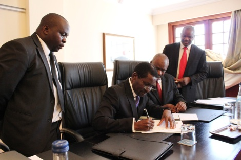 Hon. Ephraim Chiume, Minister for Foreign Affairs of the Republic of Malawi (2nd left), signs the Joint Letter of Application seeking mediation of the Lake Nyasa border dispute with Tanzania, while the Malawi Attorney General Anthony Kamanga (2nd right) witnessing the occasion, together with two Legal Service Officers from the Malawi Government. (December 2012 Tanzania's Ministry of Foreign Affairs and International Cooperation Blog)