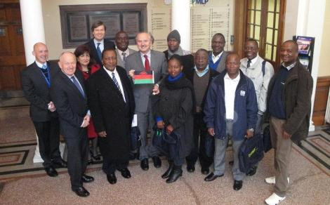 "Nine government officials participated in an ""interactive knowledge transfer"" at the University of Dundee's Centre for Energy, Petroleum and Mineral Law and Policy this week. Director of the Centre, Professor Peter Cameron is feature centre, holding the Malawian flag (Photo courtesy of CEPMLP News)"