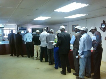 Parliamentarians and journalists queue up for lunch during the Kayelekera Uranium Mine visit