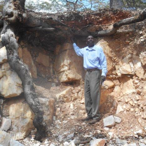 Youth Action Against Climate Change Board Chairperson, Mr Edward Nkhata, examines pits left by miners in Tchemba Forest